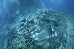 Scuba divers exploring ship wreckage. Stock Photos