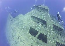 Scuba divers exploring a shipwreck Stock Image