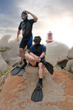 Scuba divers on island. Two scuba divers on island with lighthouse and sunset in the background Royalty Free Stock Images