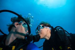 Scuba divers kissing each other underwater. Couple of scuba divers kissing each other underwater Royalty Free Stock Photos