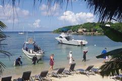 Scuba divers and land tourist Stock Images
