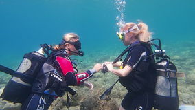 Scuba Divers. Loutra,Greece - JULY 26 2014:Scuba diving instructor teaching her student to dive.Scuba diving is an adventure sport carried out in most countries