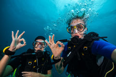 Scuba divers showing OK sign underwater. Couple of scuba divers showing OK signal underwater Royalty Free Stock Images