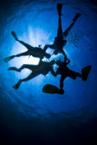Scuba divers in silhouette Stock Photo