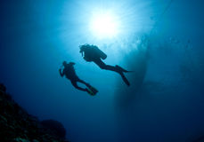 Scuba Divers Silouetted By Sun Ball Royalty Free Stock Photography