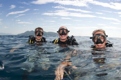 Scuba divers on surface befor dive. Scuba divers on surface before dive with island behind royalty free stock images