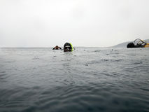 Scuba divers on the surface. Rainy day. Stock Photo