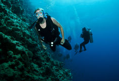 Scuba divers swim in the blue hole,Dahab. Male scuba diver swims on a wall in red sea Stock Photography