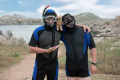 Scuba divers with teddy bear. Two scuba divers posing with teddy bear on island Stock Photos