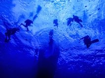 SCUBA Divers Underwater at Safety Stop Below Ship Stock Photo