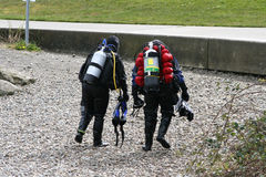 Scuba Divers v1. Scuba Divers is a capture of two divers that have just finished their lesson and are walking back across a rocky beach Stock Photo