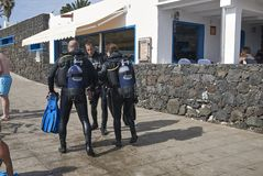 Scuba divers waliking in Puerto Calero. Lanzarote, Spain - August 21, 2015 : Scuba divers waliking  in Puerto Calero in Lanzarote Royalty Free Stock Image