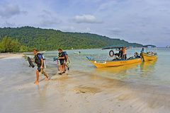 Scuba Divers walking on beach after a dive trip. KUALA BESUT, MALAYSIA  - MAY 18: Scuba Divers walking on beach after a dive trip in Perhentian Islands on May 18 Royalty Free Stock Photo