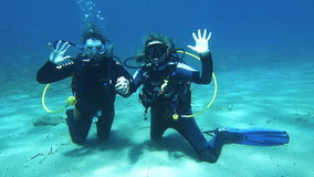 Scuba Divers Waving. Halkidiki,Greece- JULY 19 2014:Scuba diving instructor with her student having fun under the water.Scuba diving is an adventure sport stock footage