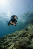 Scuba-Diving. A female scuba diver is swimming underwater above an an rocky reef. Deep blue water background stock photos