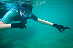 Scuba-diving. Snorkelling woman pointing forward in clear tropical water Stock Images