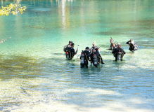 Scuba Diving Class in Florida Spring. PONCE DE LEON, FLORIDA-OCTOBER 21, 2016: Men wearing wet suits and carrying air tanks on their backs are receiving scuba stock images