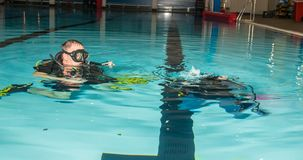Scuba diving course pool teenager girl with instructor in the water. Scuba diving course pool teenager girl with instructor do exercises in the warm water of the Stock Image