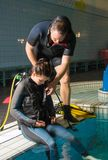 Scuba diving course pool teenager girl with instructor in the water. Scuba diving course pool teenager girl with instructor do exercises in the warm water of the Royalty Free Stock Photography