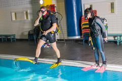Scuba diving course pool teenager girl with instructor  on the waterfront for. Scuba diving course pool teenager girl with instructor do exercises  on the Stock Photo