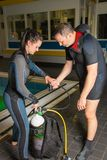 Scuba diving course pool teenager girl with instructor  on the waterfront for. Scuba diving course pool teenager girl with instructor do exercises  on the Royalty Free Stock Image
