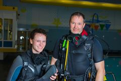 Scuba diving course pool teenager girl with instructor  on the waterfront for. Scuba diving course pool teenager girl with instructor do exercises  on the Stock Photography