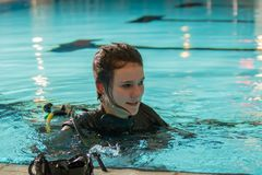 Scuba diving course pool teenager girl with instructor. Goes underwater and holds the inflator hose Stock Photos