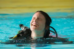 Scuba diving course pool teenager girl with instructor. Goes underwater and holds the inflator hose Stock Images