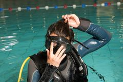 Scuba diving course pool teenager girl with instructor. Goes underwater and holds the inflator hose Royalty Free Stock Photography