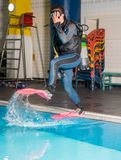 Scuba diving course pool teenager girl with instructor. Goes underwater and holds the inflator hose Royalty Free Stock Images