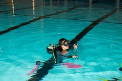 Scuba diving course pool teenager girl with instructor. Goes underwater and holds the inflator hose Royalty Free Stock Photo