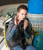 Scuba diving course pool teenager girl with instructor. Is waiting before she can swim underwater and build up the dive set Royalty Free Stock Images