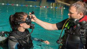 Scuba diving course pool teenager girl with instructor in the water. Scuba diving course pool teenager girl with instructor do exercises in the warm water of the Stock Photography