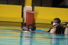 Scuba diving course pool teenager girl with instructor in the water. Scuba diving course pool teenager girl with instructor do exercises in the warm water of the Stock Photo