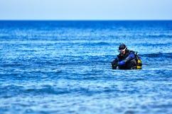 Scuba diving. Scuba diver preparing to dive into sea Stock Photo