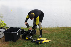 Scuba diving. Diver in wetsuit, controlling his equipment Royalty Free Stock Photography