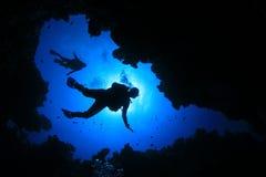 Scuba Diving. Scuba divers descend into underwater cave royalty free stock photo