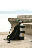 Scuba diving equipment. Closeup of scuba diving jacket and oxygen tank with ocean in background Royalty Free Stock Photo