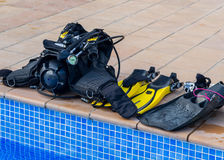 Scuba diving equipment on the edge of a pool Royalty Free Stock Image