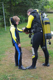 Scuba diving. Father and son preparing for scuba diving royalty free stock photos
