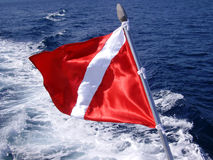 Scuba diving flag. Scuba diving red and white flag flying off the back of a dive boat Royalty Free Stock Photography