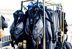 Scuba diving gear ona a stand in diving center. Buoyancy compensators and regulators are ready for beginner or advanced diving course. Drying and washing the stock photo