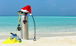 Scuba diving gear on tropical beach with a christmas hat Royalty Free Stock Image