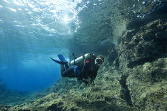 Scuba-Diving in shallow water. A scuba diver is exploring an underwater reef landscape in shallow water. turkish sea royalty free stock image