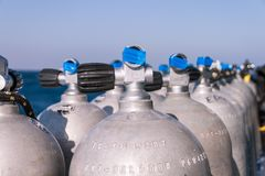 Scuba Diving Tanks with Blue Tape and Sea in the Background stock photo