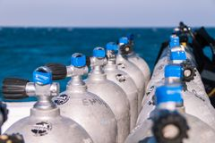 Scuba Diving Tanks with Blue Tape and Sea in the Background stock photography