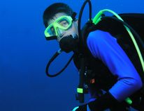 Scuba diving teenager. A young boy scuba diving. He is posing for the camera over 80ft deep underwater stock photos