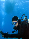 Scuba-duiker die Maten controleert onder de Boot stock afbeelding