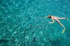 Scuba-duiker met vinnen die in het overzees in duidelijk water drijven, stock afbeeldingen