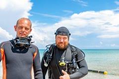 Scuba-duikers in een kostuum voor het duiken hebbend pret stock foto